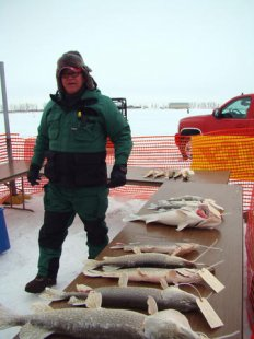 Devils Lake Fire Chief Jim Moe appears next to a few of the seafood caught during last many years fishing tourney.