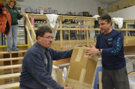 Stewart Workman (left) and Dave Carraro unload a box of gear from Tuna.com under Alice Workman's watchful attention. PICTURE with STEPHEN RAPPAPORT